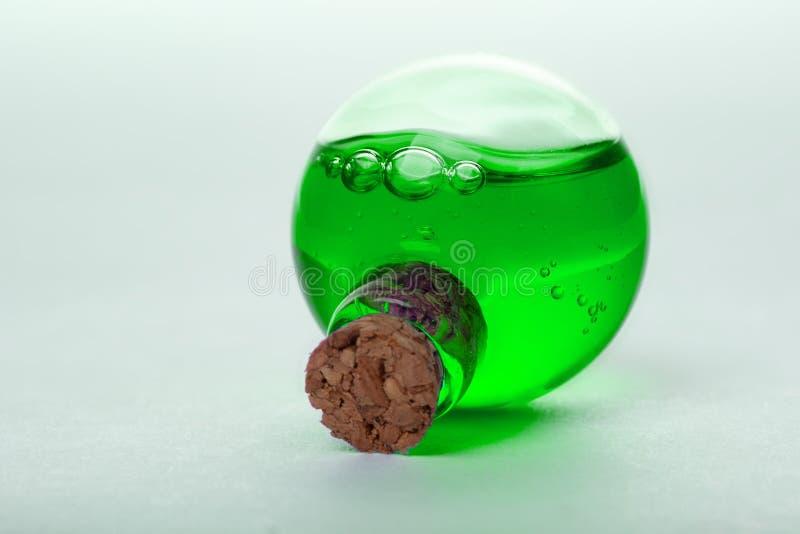 Grön flytande i liten medicinflaska för gammal stil fotografering för bildbyråer