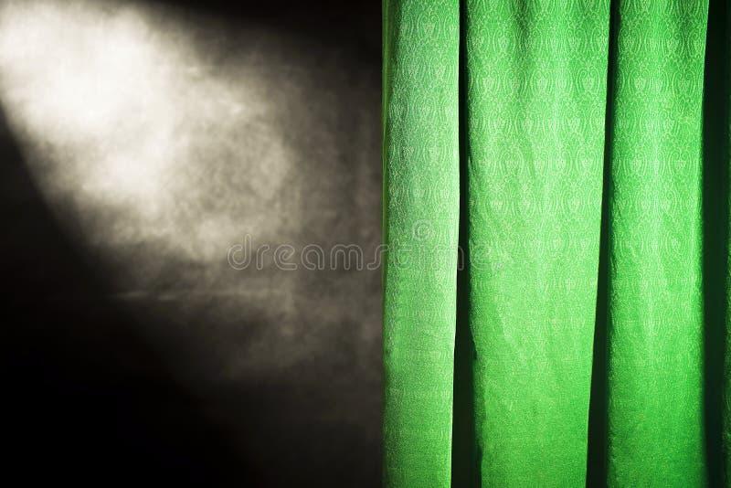 Grön gardin mot en svart bakgrund med det bästa reflektorljuset royaltyfri fotografi
