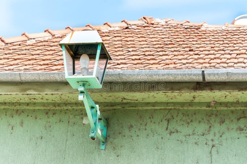 Grön gatalampa eller lykta på fasaden för yttre vägg av huset som ger ljus på natten royaltyfri foto