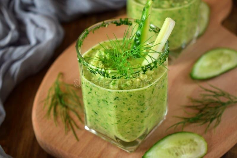 Grön gazpacho i ett exponeringsglas arkivbild