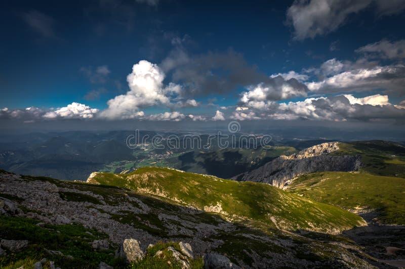 Grön gräs- raxplatå med den stora lappen av skugga och dramatiskt, molnigt, mörkt - blå himmel arkivfoto