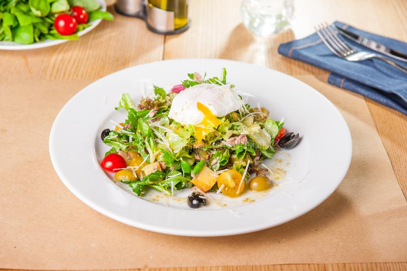 Grön grönsaksallad med tonfisk och det tjuvjagade ägget på den vita plattan på den trätjänade som tabellen Selektiv fokus, kopier royaltyfri bild