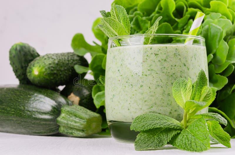 Grön grönsaksmoothie i exponeringsglas med djupt - gröna grönsaker och sugrör, mintkaramell, closeup arkivfoto