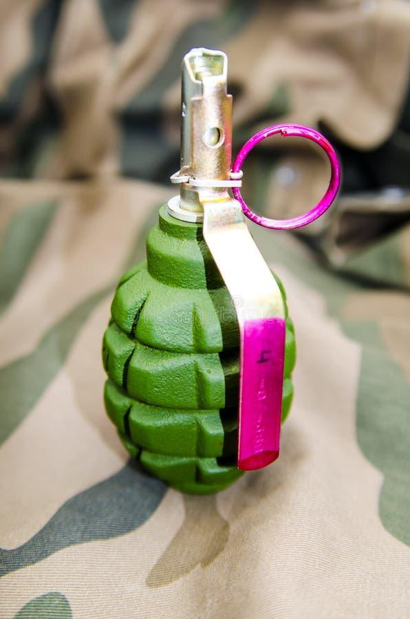 Grön granat på kamouflagebakgrunden closeup arkivfoton
