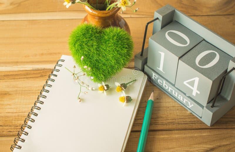 grön hjärta med den wood kalendern för tappning för Februari 14, noteboo arkivfoton