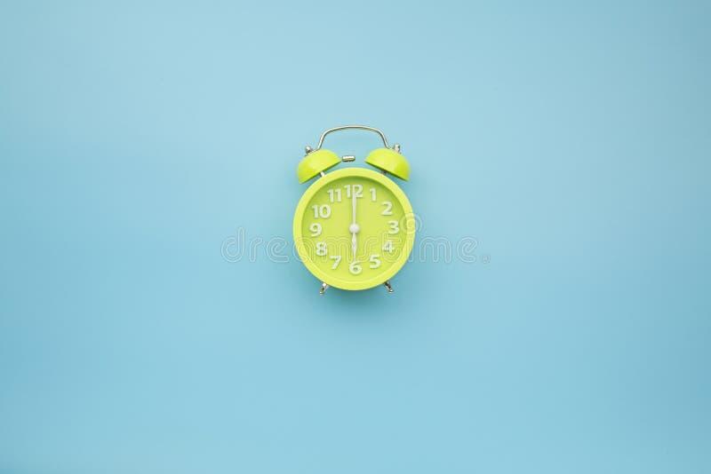 Grön klocka på sex gång för nolla-`-klocka på pastell för mittblåttbakgrund fotografering för bildbyråer