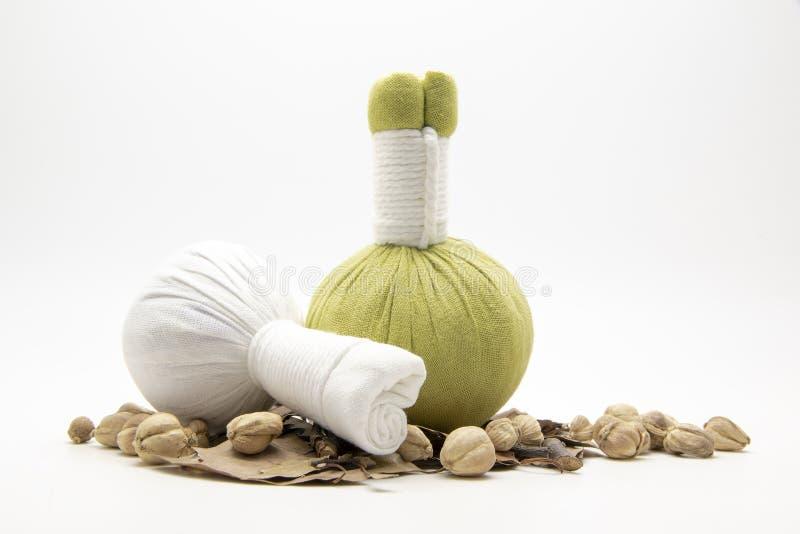 Grön kompressboll, vit kompressboll och örter på vitbaksida royaltyfria bilder