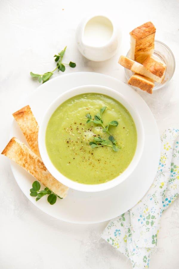 Grön kräm- broccoli för grönsaksoppa, ärtor, zucchini, spenat) med rostat bröd, krutonger Läcker vegetarisk sund vår sommar royaltyfri bild