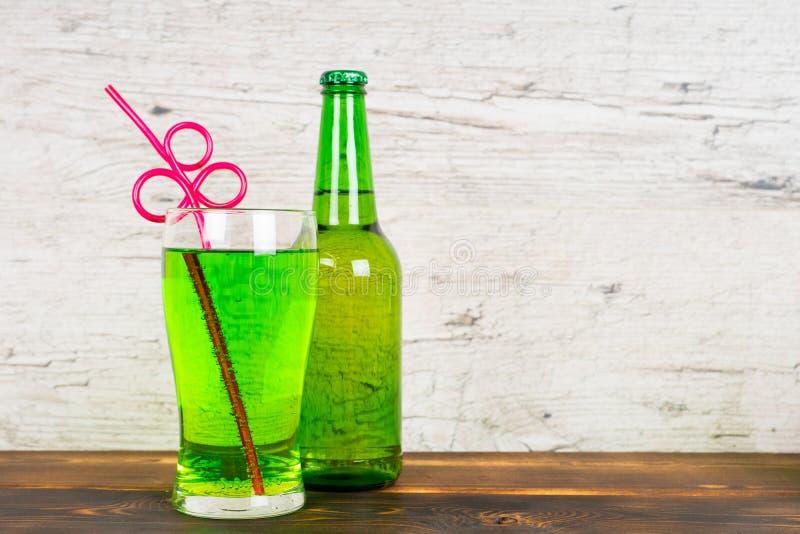 Grön läsk med den coctailröret och flaskan royaltyfri fotografi