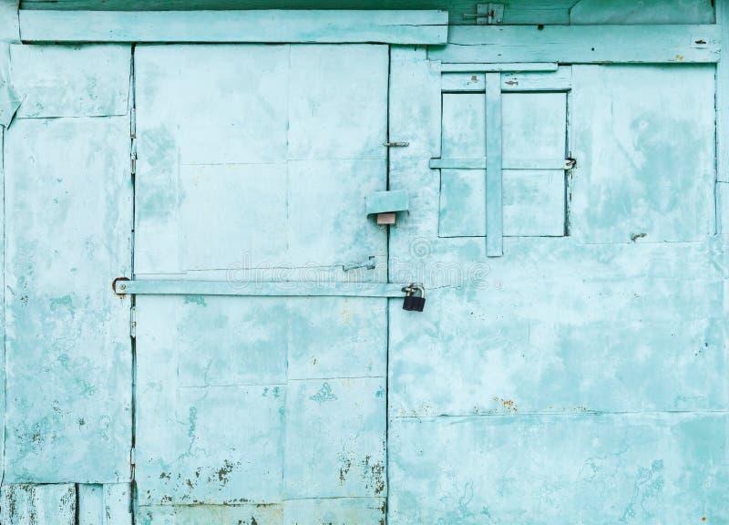 Grön lantlig vägg med den låsta dörren och fönstret arkivbild