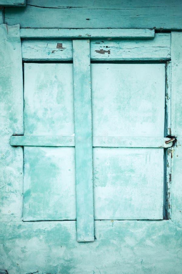 Grön lantlig vägg med det låsta fönstret arkivbild