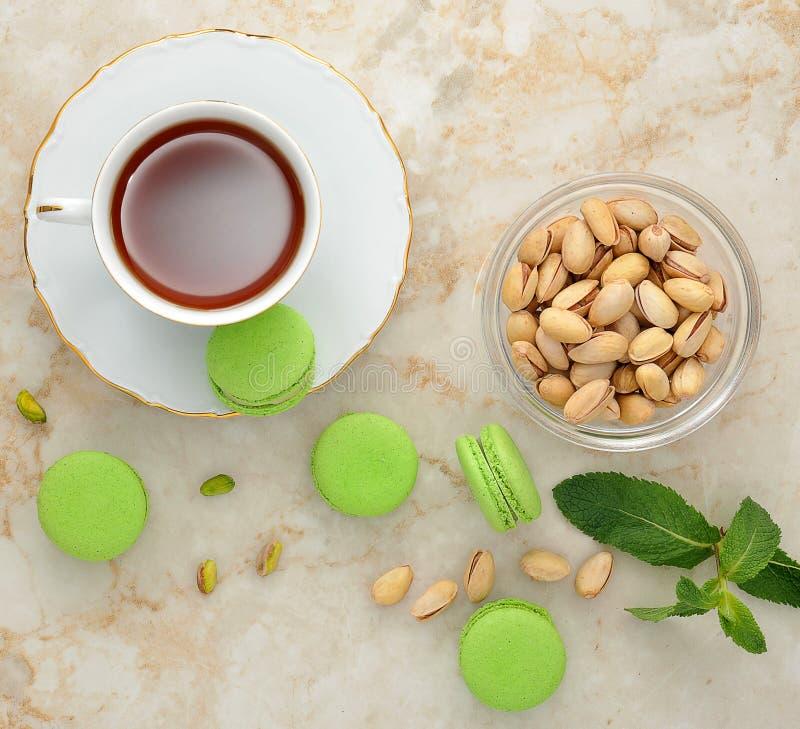 Grön macaron med en kopp te fotografering för bildbyråer