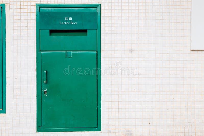 Grön metallbrevlåda och vitvägg royaltyfri fotografi