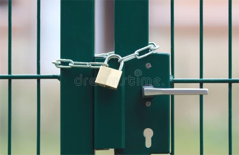Grön metallport som är låsta med kedjan och hänglåset royaltyfri fotografi