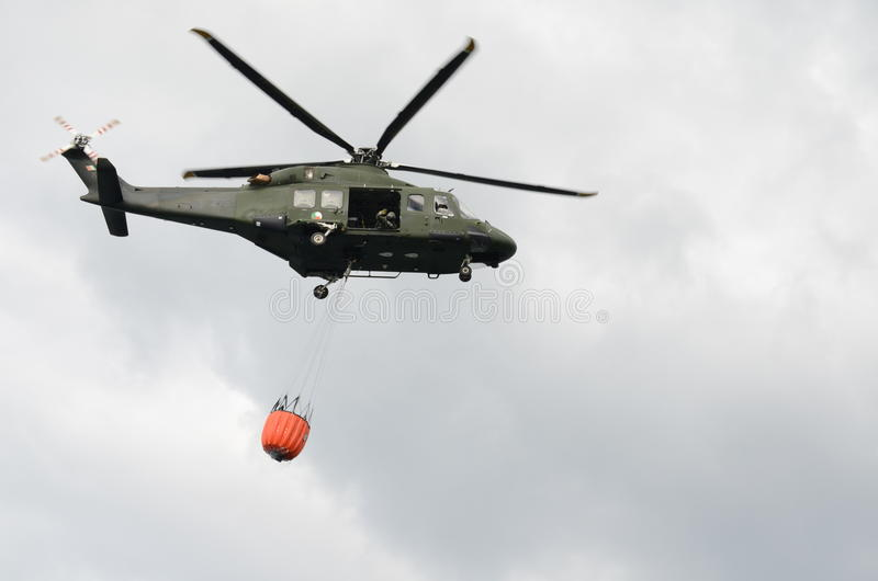 Grön militär helikopter som bär en orange vattenhink arkivfoto