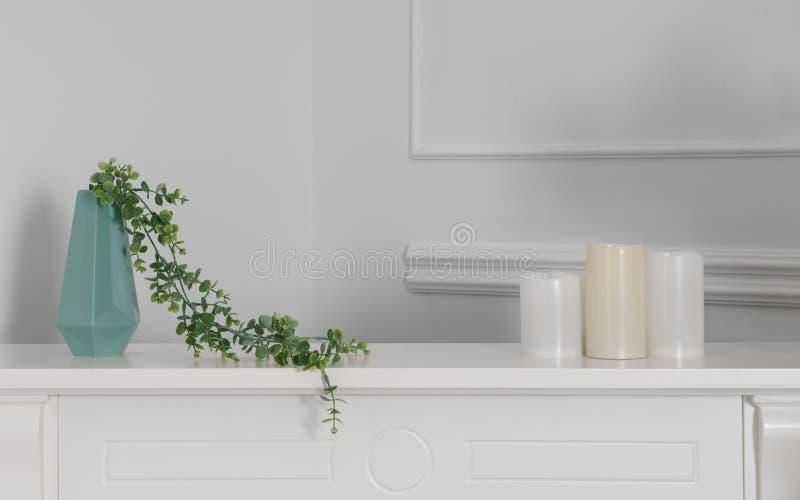 Grön modern vas med tre stearinljus på den vita räknaren royaltyfria bilder