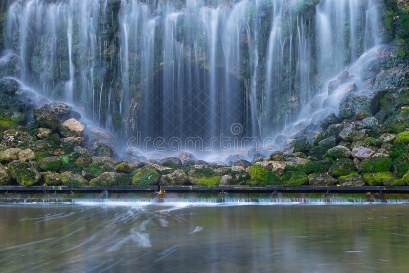 Grön mossa täckte stenar i vattenfall royaltyfri bild