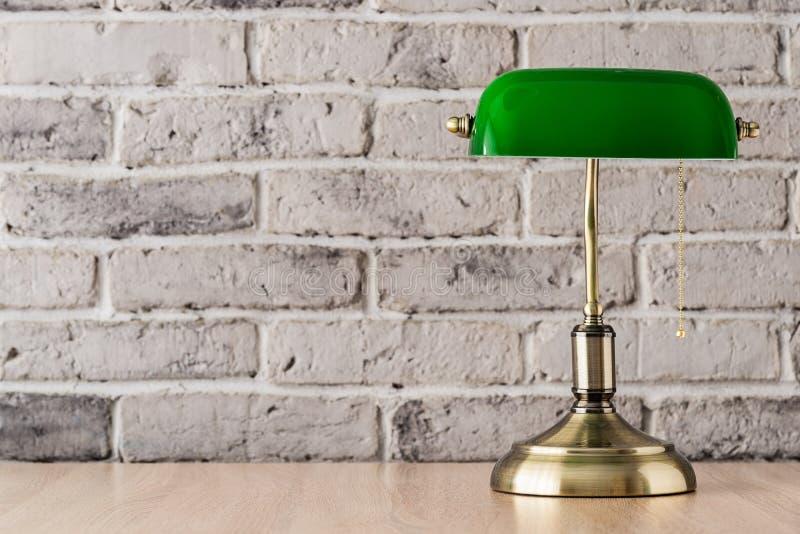 Grön och guld- bankirlampa på skrivbordet fotografering för bildbyråer