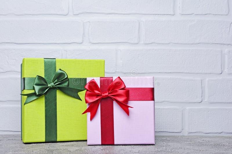 Grön och purpurfärgad klassisk gåvaask med den röda satängpilbågen och kopieringsutrymme arkivfoto