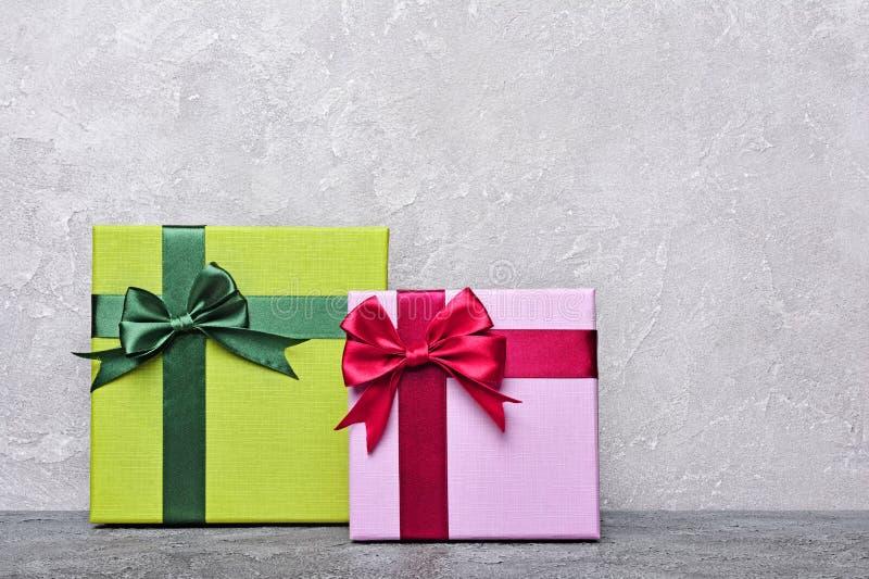 Grön och purpurfärgad klassisk gåvaask med den röda satängpilbågen och kopieringsutrymme arkivfoton