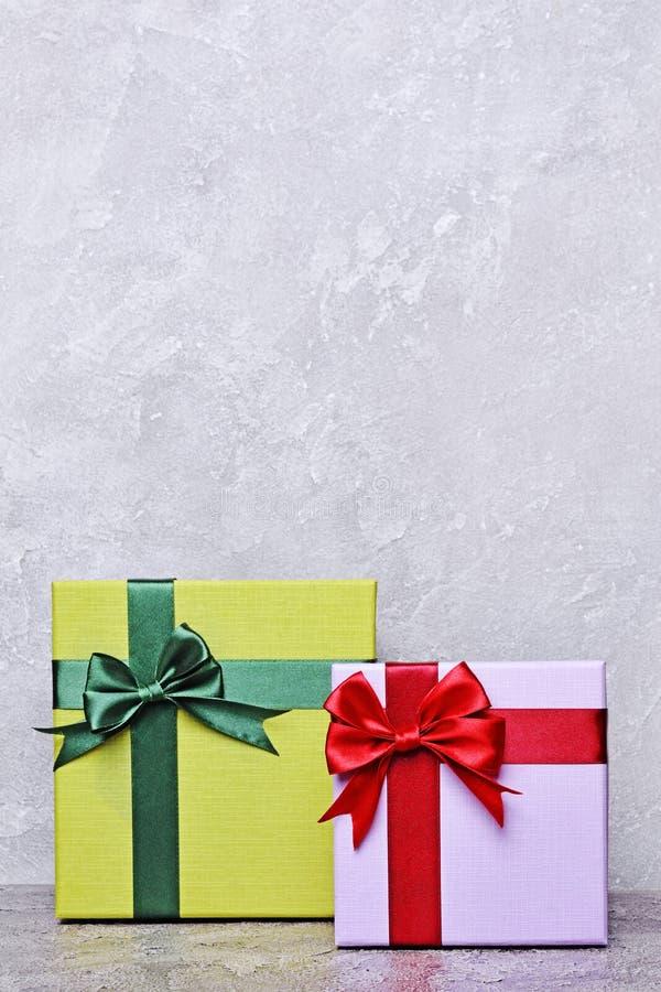 Grön och purpurfärgad klassisk gåvaask med den röda satängpilbågen och kopieringsutrymme arkivbilder
