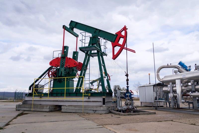 Grön och röd pumpjack, oljahäst, oljaborrtorn som pumpar oljabrunnen med dramatisk bakgrund för molnig himmel fotografering för bildbyråer