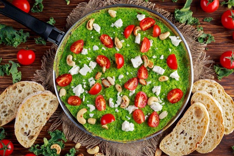 Grön omelett för grönsak med tomater, grönkål, grekisk ost, oliv, muttrar, rostat bröd på träbakgrund Sund mat för begrepp royaltyfri foto