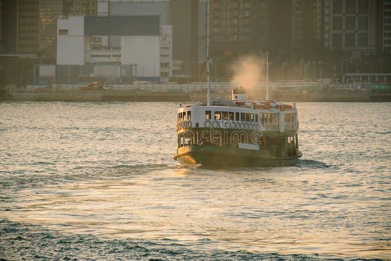 Grön passagerarfärja i den victoria hamnen med cityscapebakgrund mot morining soluppgång, service mellan Kowloon och Hong royaltyfri foto
