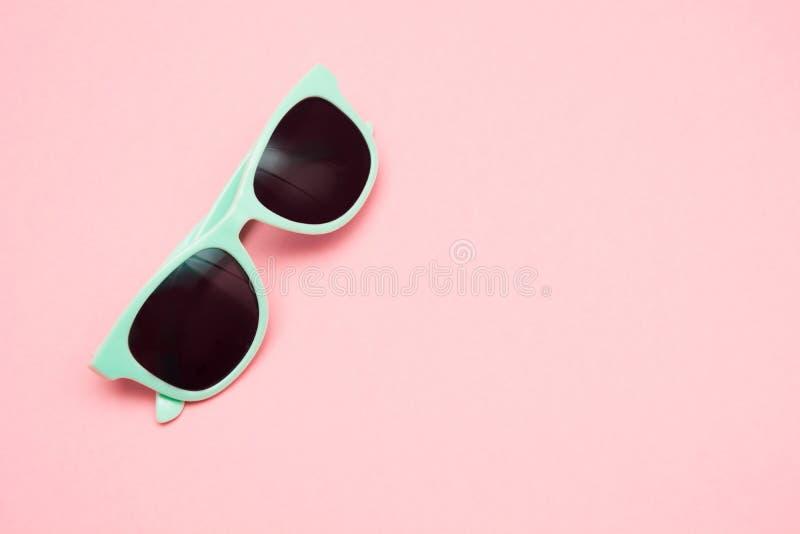 Grön pastellfärgad solglasögon som isoleras på punchy rosa färger, bästa sikt kopiera avstånd sommar för snäckskal för sand för b arkivfoto