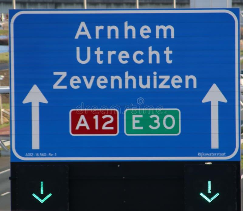 Grön pil ovanför den körande gränden som indikerar att dess öppet på överskriften för motorway A12 E30 Arnhem, utrecht och Zevenh royaltyfri foto