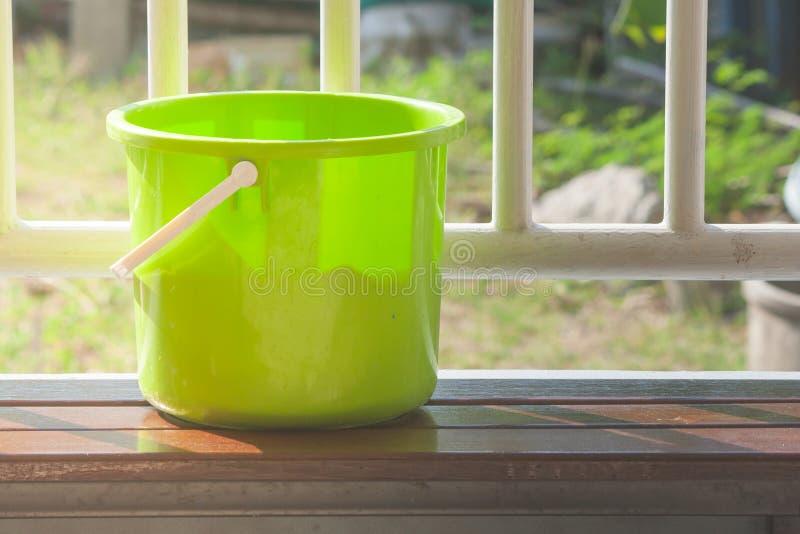 Grön plast- vattenhink eller pålagd trälång stol för hink med det vita stålstaketet i bakgrunden royaltyfri bild