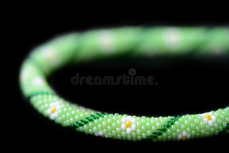 Grön prydd med pärlor halsband med blommatrycket som isoleras på en svart bakgrund royaltyfri foto