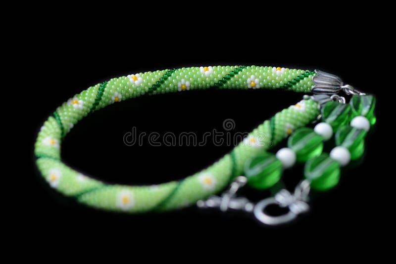 Grön prydd med pärlor halsband med blommatrycket som isoleras på en svart bakgrund royaltyfri bild