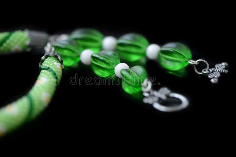 Grön prydd med pärlor halsband med blommatrycket som isoleras på en svart bakgrund royaltyfria bilder