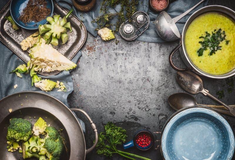 Grön Romanesco och broccolisoppa med matlagningingredienser, kökhjälpmedel, slev, bowlar och skedar på mörk lantlig bakgrund, öve royaltyfri bild