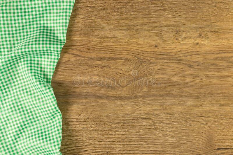 Grön rutig torkdukeservett på träbakgrund royaltyfri foto