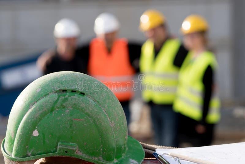 Grön säkerhetshjälm på förgrund Grupp av fyra byggnadsarbetare som poserar på ut ur fokuserad bakgrund fotografering för bildbyråer