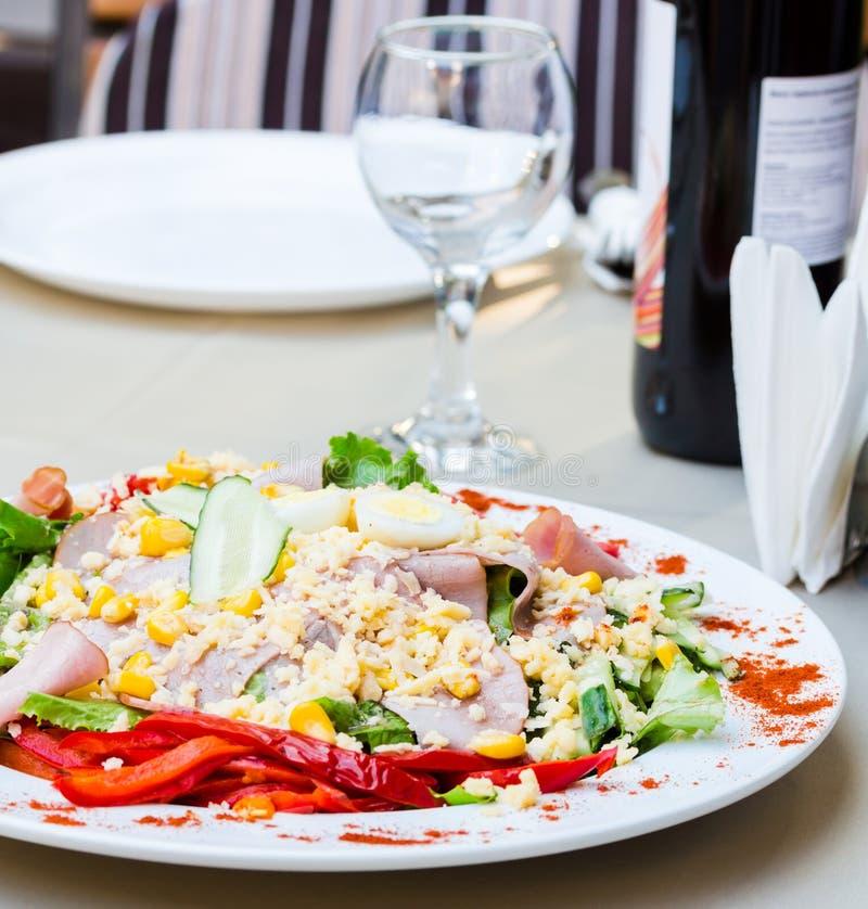Grön sallad med skinka, ägget, havre och peppar på den vita tablecloen arkivbilder