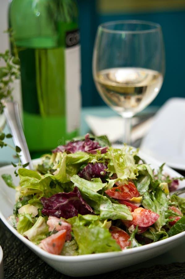 Grön sallad och exponeringsglas av vitt vin royaltyfri fotografi