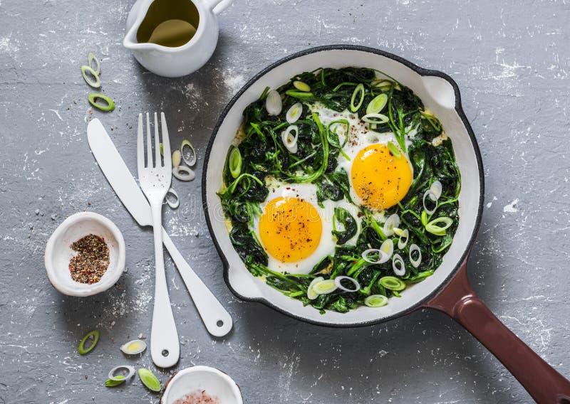 Grön shakshuka Stekte ägg med nya spenat, ramson, purjolök i en panna på en grå bakgrund royaltyfri fotografi