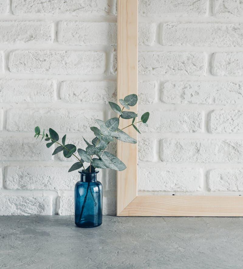 Grön sidaeukalyptus i en blå vas och träphotoframe mot en vit minimalism för stil för tegelstenvägg skandinavisk royaltyfria foton