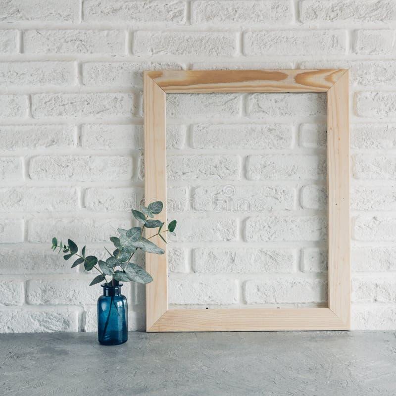 Grön sidaeukalyptus i en blå vas och träphotoframe mot en vit minimalism för stil för tegelstenvägg skandinavisk arkivbild