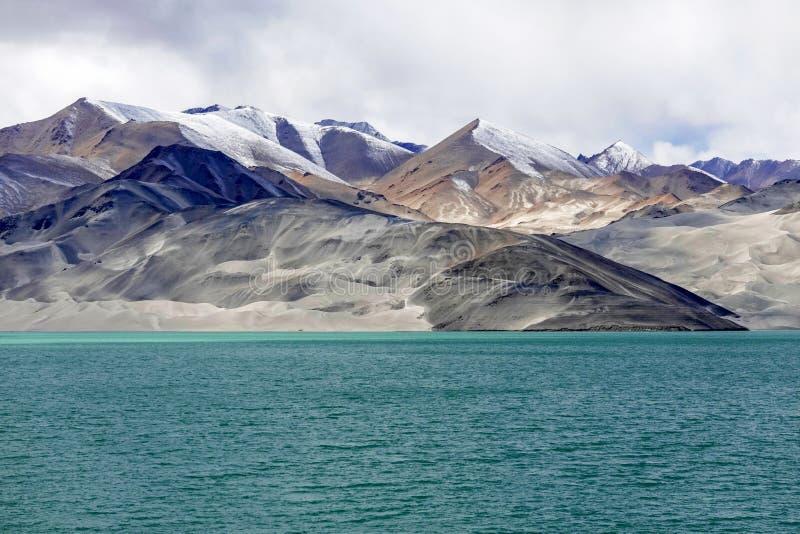Grön sjö, snöberg, vita moln, blå himmel arkivbilder