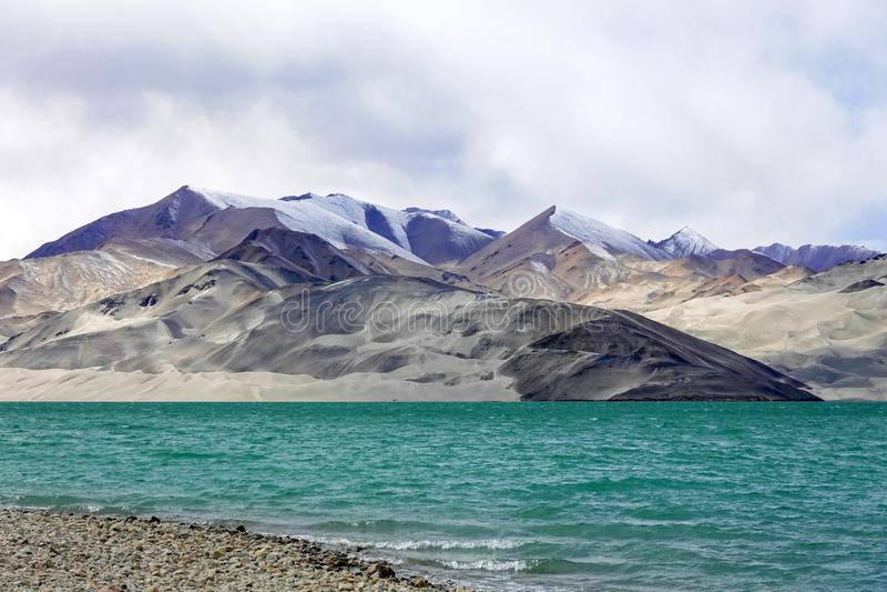 Grön sjö, snöberg, vita moln, blå himmel royaltyfria foton