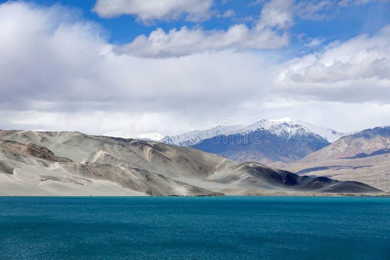 Grön sjö, snöberg, vita moln, blå himmel arkivfoton