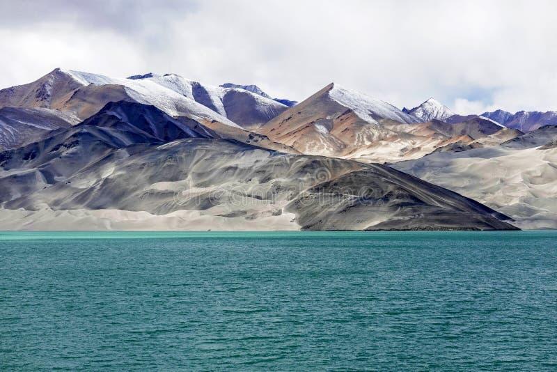 Grön sjö, snöberg, vita moln, blå himmel i Pamirrs royaltyfri bild