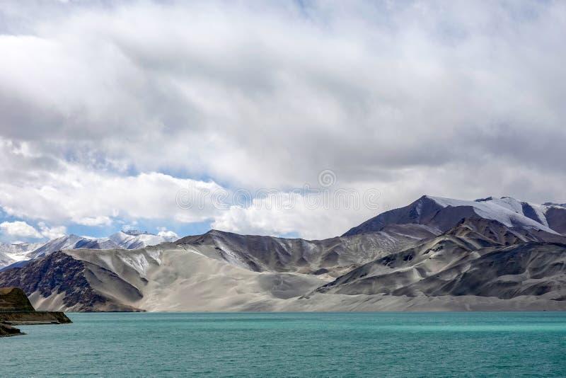 Grön sjö, snöberg, vita moln, blå himmel i Pamirrs arkivbilder