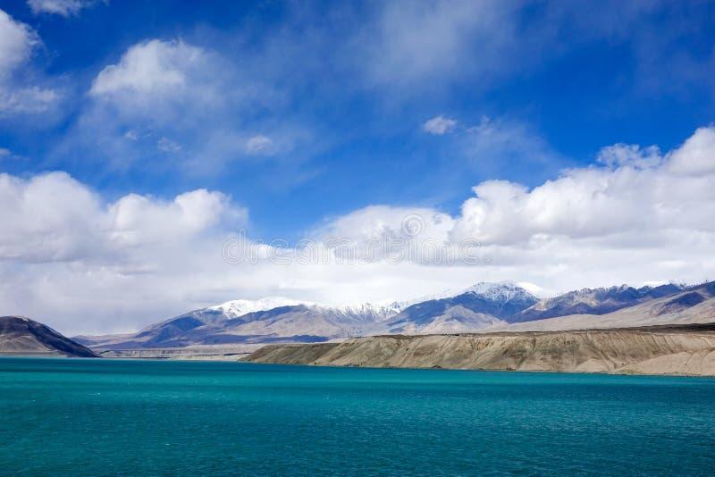 Grön sjö, snöberg, vita moln, blå himmel i Pamirrs royaltyfri fotografi