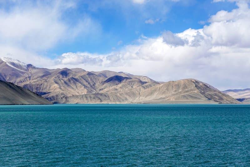 Grön sjö, snöberg, vita moln, blå himmel i Pamirrs arkivfoton