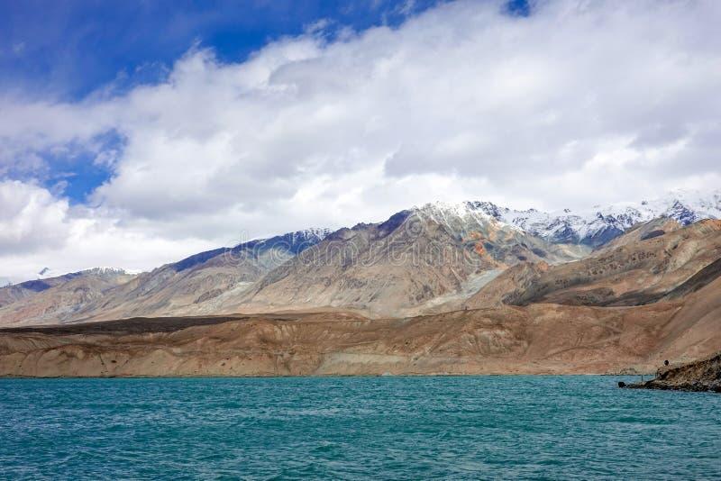 Grön sjö, snöberg, vita moln, blå himmel i Pamirrs fotografering för bildbyråer